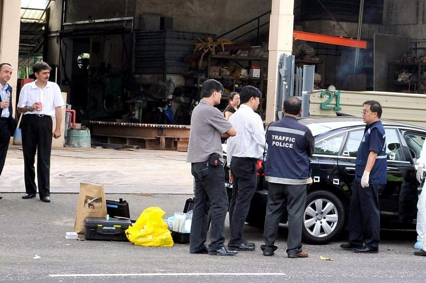Uniformed officials surrounding a car that was found abandoned at Sungei Kadut Avenue. The car, a black Audi A6, was involved in a horrific double hit-and-run accident on Bukit Panjang Road. The car belongs to the Romanian embassy here, and it was re