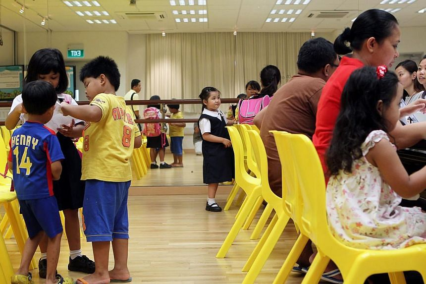 A boy plays with his siblings while his parents register him for pre-school at Punggol View Primary School. The Ministry of Education has decided to cut by as much as half the number of new enrolments at four of its five kindergartens next year. -- S