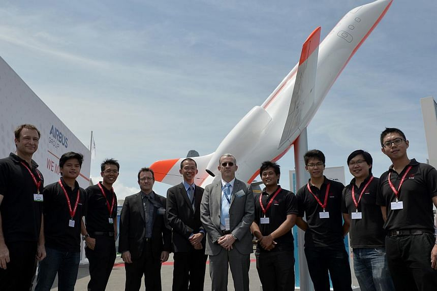 Hope Technik's Peter Ho (fifth from left), Airbus' Christophe Chavagnac (fourth from left) and some of Hope's engineers with a model of the plane the two companies are working on. -- ST PHOTO: MUGILAN RAJASEGERAN