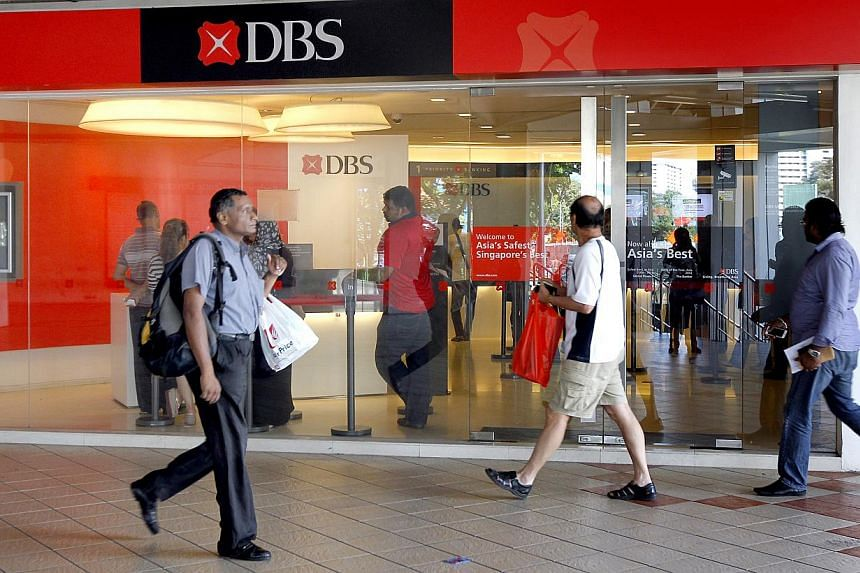 People walk past the DBS branch at Rochor Centre. DBS, South-east Asia's biggest lender, logged a 6 per cent rise in fourth-quarter net profit over a year ago. -- ST FILE PHOTO: CHEW SENG KIM