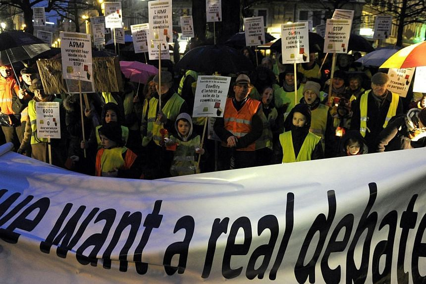 """Protesters, who call themselves the """"yellow jackets"""", hold banners and placards as they demonstrate against a new law authorizing euthanasia for children, in Brussels February 11, 2014. -- PHOTO: REUTERS"""