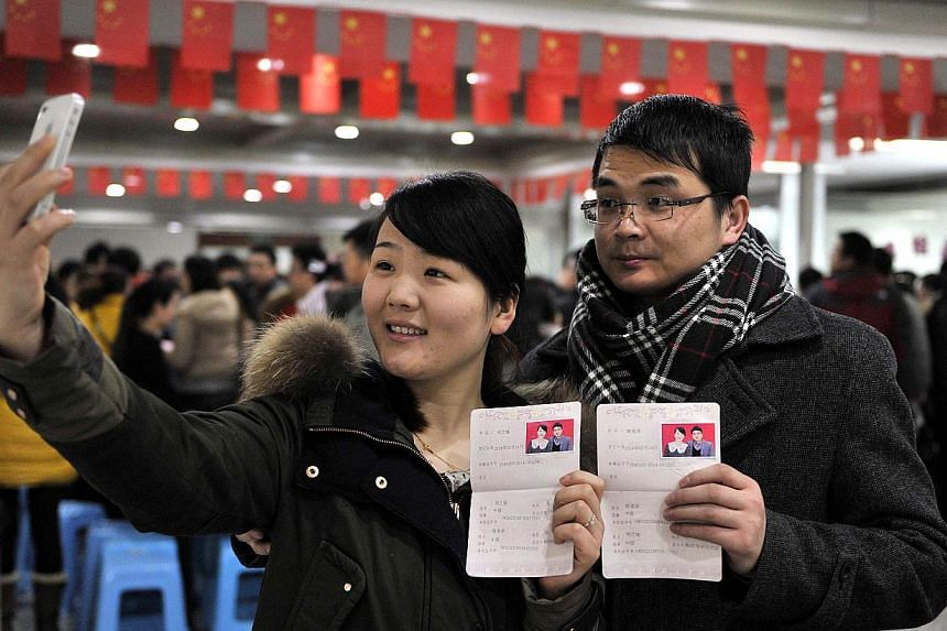 A couple pose for pictures with their marriage certificates at a civil affairs bureau in Hefei, Anhui province, on February 14, 2014. According to local media, many young couples rushed to register their marriages on Friday as the last day of Chinese