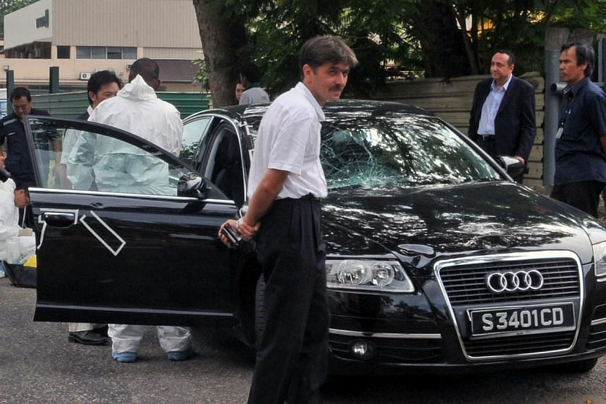 Romanian embassy official Dr Silviu Ionescu (second from right in the background) and his driver Marius Trusca (centre in the foreground) watching as police inspect the black Audi saloon, in this photo taken on Dec15,2009. -- ST FILE PHOT