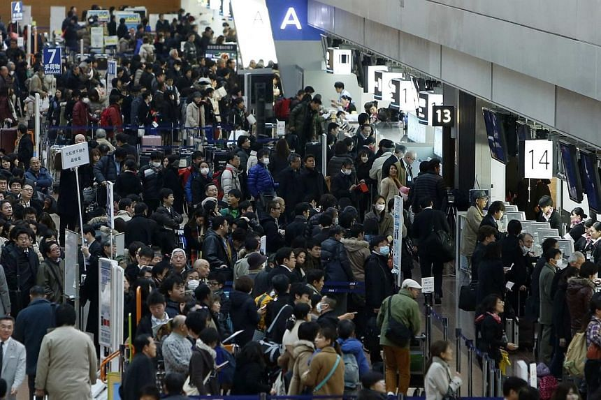 People lines up in front of check in counters as flights are delayed and cancelled due to snow falls at Haneda airport in Tokyo, Feb 14, 2014.A snow storm hit Japan on Friday, Feb 14, 2014, disrupting rail and road travel, grounding more than 1