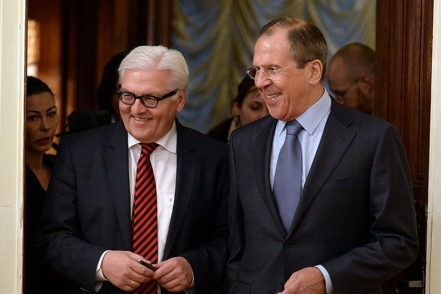 """Russian Foreign Minister Sergei Lavrov (right) speaks with his German counterpart Frank-Walter Steinmeier during their meeting in Moscow, on Feb 14, 2014. MrLavrov on Friday, Feb 14, 2014, rebuked the European Union for trying to extend its """"sp"""