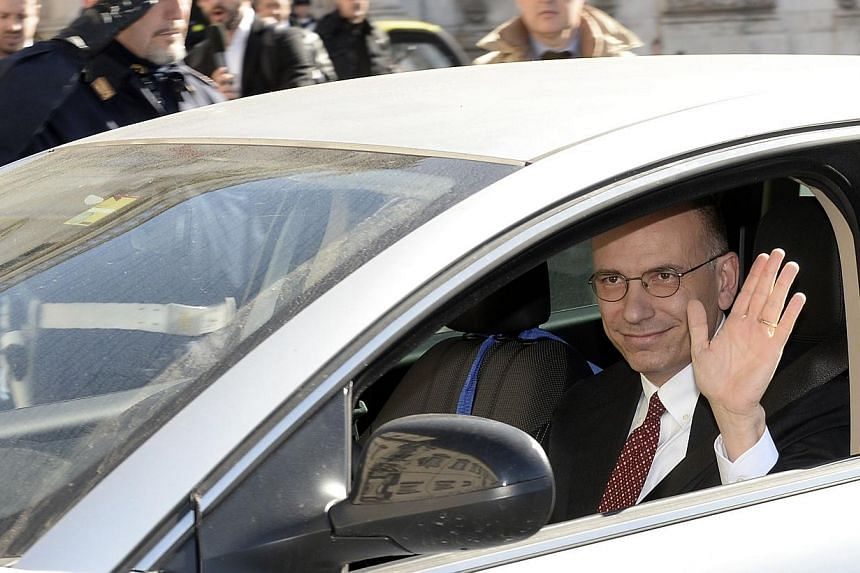 Italian Prime Minister Enrico Letta waves as he arrives at Quirinale palace in Rome to formally submit his resignation, on Feb 14, 2014.Mr Letta has submitted his resignation to President Giorgio Napolitano, who will hold consultations on Frida