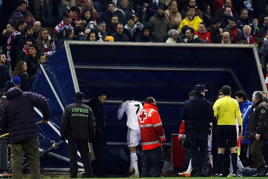 Real Madrid's Cristiano Ronaldo (No. 7) grabs his head after being hit with a lighter upon leaving the field at the end of the first half of their Spanish King's Cup semi-final second leg soccer match against Atletico Madrid at Vicente Calderon stadi