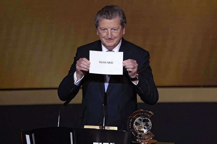 England manager Roy Hodgson unveils the name of Germany's coach Silvia Neid as the winner of the 2013 FIFA Women's Coach of the Year award during the FIFA Ballon d'Or award ceremony at the Kongresshaus in Zurich, on Jan 13, 2014. Hodgson has got the