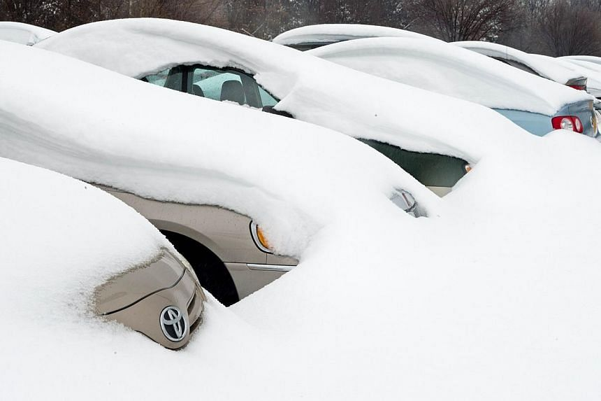 Cars of travelers are covered in deep snow, on Feb 13, 2014, at the long term parking lot at Dulles International Airport (IAD) in Virginia near Washington, DC. A deadly winter storm swept the eastern United States on Thursday, Feb 13, 2014, spelling