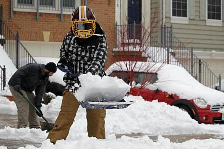 Local residents shovel snow in front of their houses, on Feb 13, 2014, in Alexandria, Virginia. The Washington, DC, area is embracing the biggest sown storm in four years.  -- PHOTO: AFP