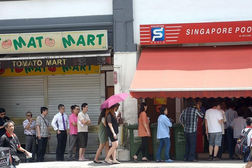 Punters queuing up at a Singapore Pools outlet at Geylang Lor 25. -- ST PHOTO: JAMIE KOH