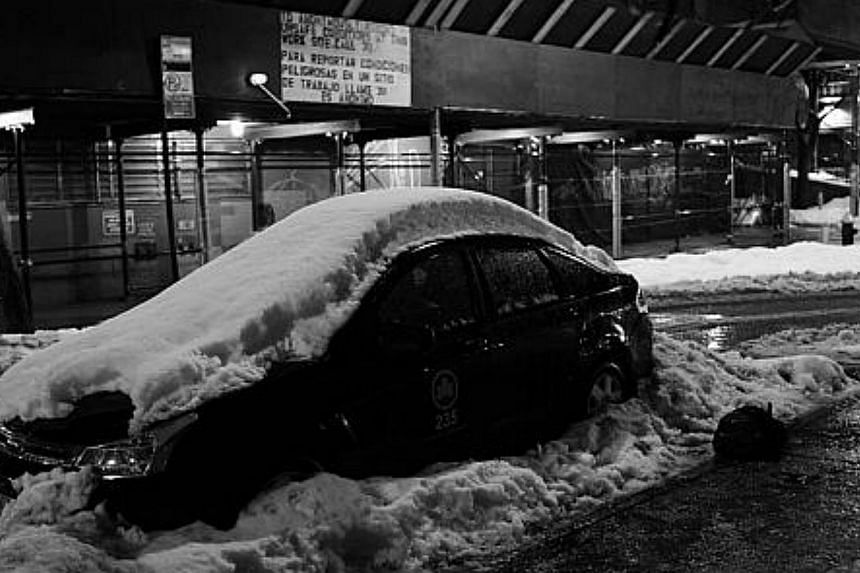 A snow covered car is parked on the street, on Feb 13, 2014, in New York City. -- PHOTO: AFP