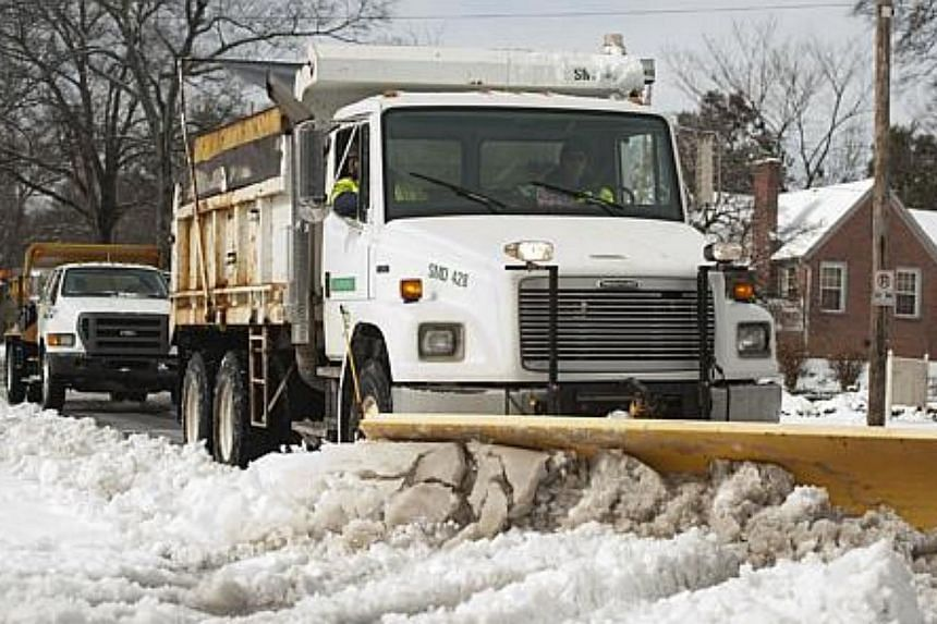 Snow scrapers and spreaders make their way through a side street around Charlotte, North Carolina, on Feb 13, 2014. -- PHOTO: AFP