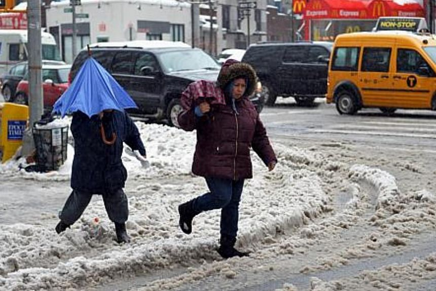 People walk through slush on a corner in the Greenwich Village area of Manhattan, on Feb 13, 2014, in New York. -- PHOTO: AFP