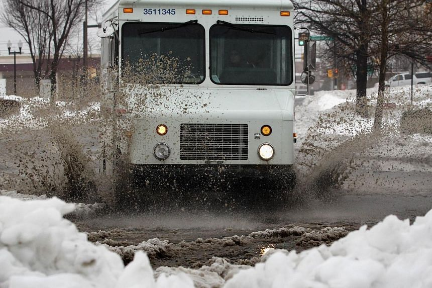 A truck passes through a water puddle, on Feb 13, 2014, in Springfield, Virginia. -- PHOTO: AFP