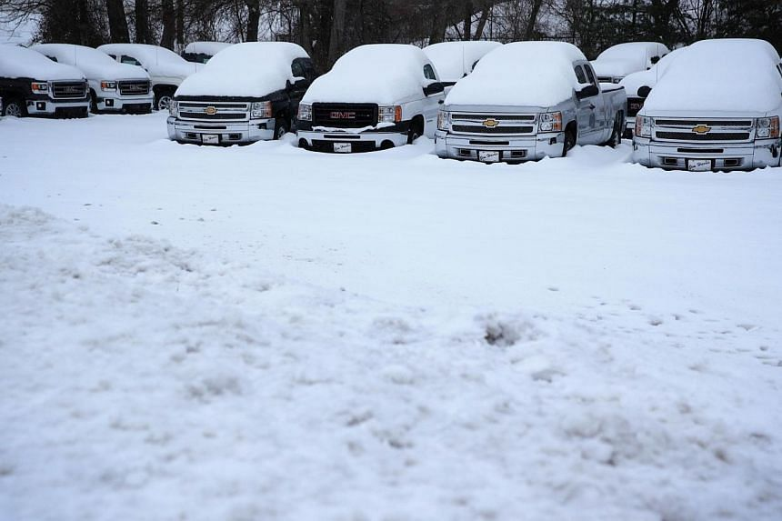 Trucks are covered with snow as they sit in a car dealer lot, on Feb 13, 2014, in Warrenton, Virginia. -- PHOTO:AFP