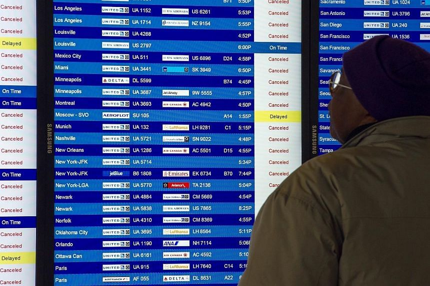n airline traveler checks the status of flights that are mostly cancelled at Dulles International Airport(IAD), on Feb 13, 2014, near Washington, DC, in Sterling, Virgina. -- PHOTO: AFP