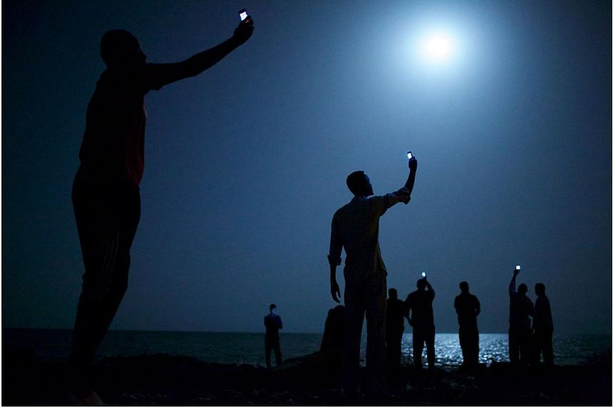 A picture of African migrants standing on the shore of Djibouti City at night, their glimmering phones held aloft to catch a weak signal, won the World Press Photo prize on Friday, Feb 14, 2014, for American photographer John Stanmeyer of the VII Pho