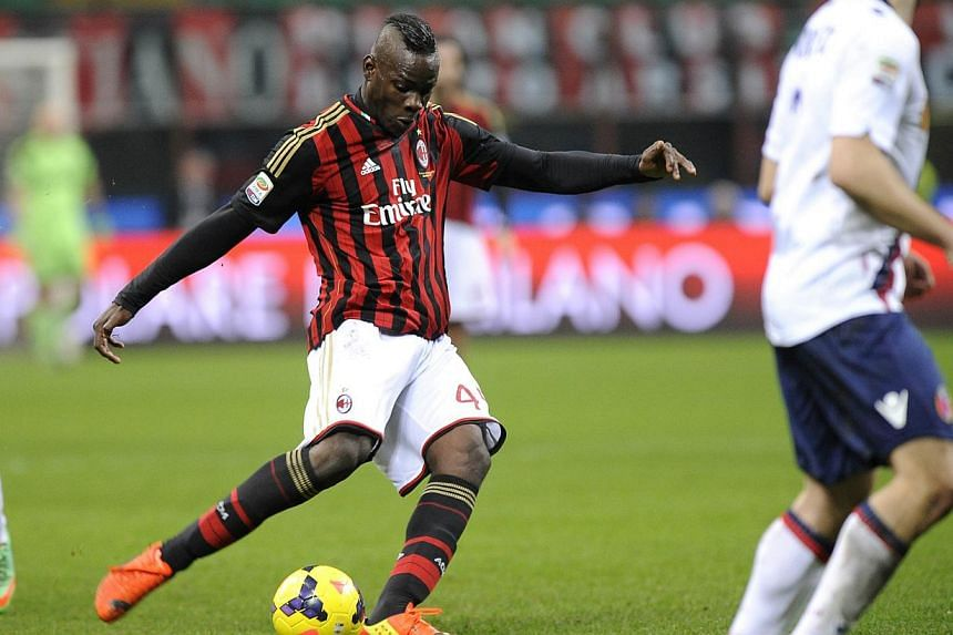 AC Milan's Mario Balotelli shoots to score against Bologna during their Italian Serie A soccer match at San Siro Stadium in Milan February 14, 2014. -- PHOTO: REUTERS