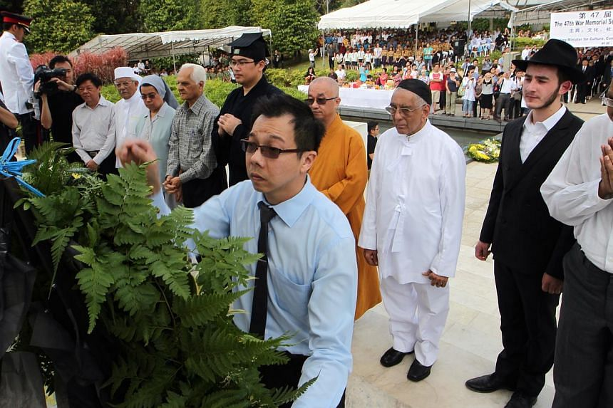 Representatives from various religious organisations lay the wreath and pay their respects in front of the Civilian War Memorial. -- ST PHOTO: NEO XIAOBIN