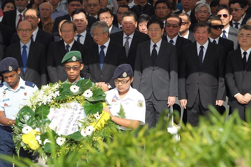 Guest-of-honour Mr Lawrence Wong and other guests watch as representatives from the National Cadet Corps prepare to lay the wreath and lay their respects.-- ST PHOTO: NEO XIAOBIN