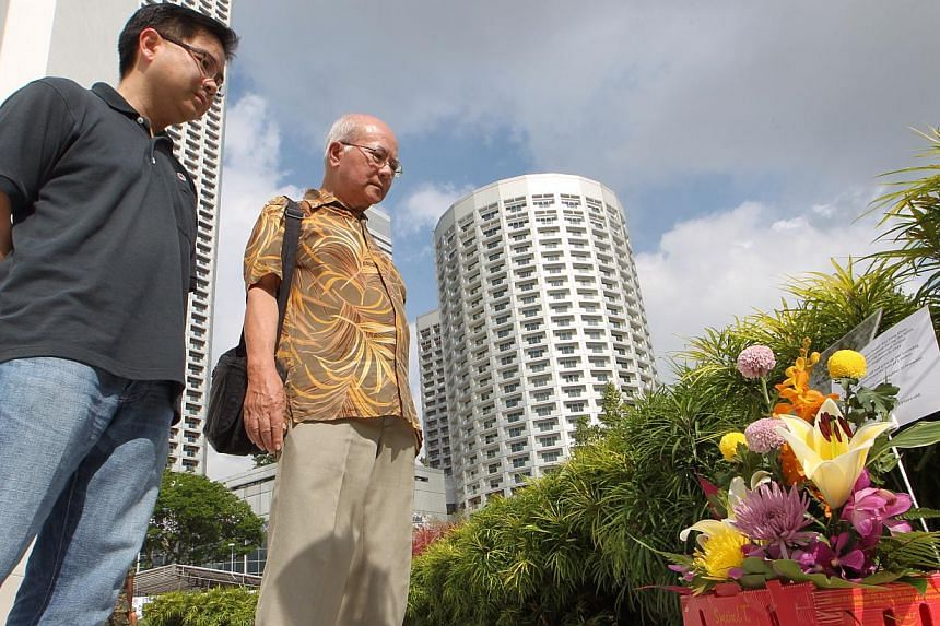 Mr Teo Hong Mong, 73, and his 40-year-old son Mr Teo Yu Ming (left) look at the flowers they brought to pay their respects to the senior Teo's father. -- ST PHOTO: NEO XIAOBIN