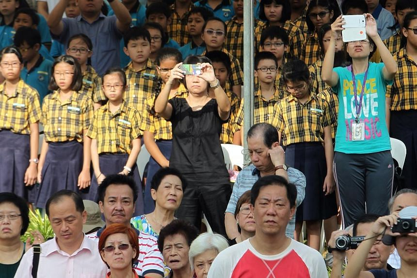 Members of the public, students and families of victims take photographs during the wreath laying ceremony during the 47th War Memorial Service in commemoration of the civilian victims of the Japanese Occupation held at the War Memorial Park along Be