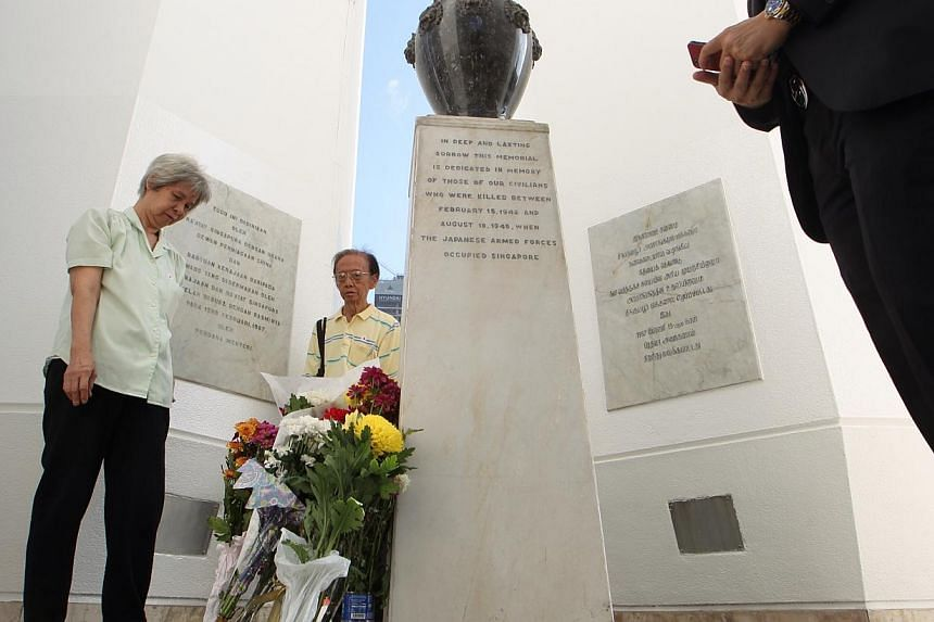 Families of the victims pay their respects in front of the Civilian War Memorial during the 47th War Memorial Service in commemoration of the civilian victims of the Japanese Occupation held at the War Memorial Park along Beach Road on Feb 15, 2014.