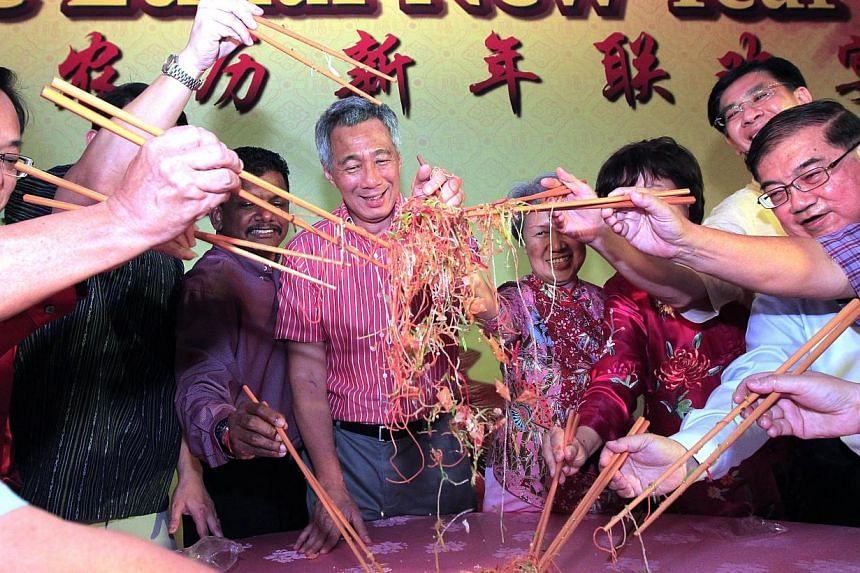 Prime Minister Lee Hsien Loong and his wife Ho Ching tossing yushengata Chinese New Year dinner in his Teck Ghee wardon Saturday, Feb 15, 2014.-- ST PHOTO: CHEW SENG KIM