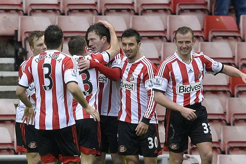 Sunderland's Craig Gardner (centre) is congratulated by teammates after scoring against Southampton in the FA Cup at the Stadium of Light on Saturday, Feb 15, 2014.His magnificent winning goal made Sunderland the first side to reach this season