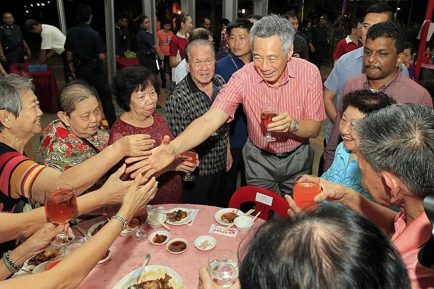 """Prime Minister Lee Hsien Loonggreeting guests ata Chinese New Year dinner in his Teck Ghee wardon Saturday, Feb 15, 2014. Singapore must remain a """"shining red dot"""" - small, but a capable and serious country - to maintain its place i"""
