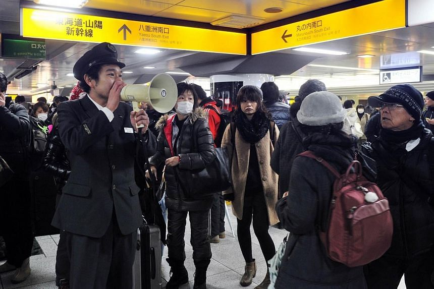 A station employee guides passengers as bullet train service is suspended at the Tokyo station, on Feb 15, 2014. -- PHOTO: AFP