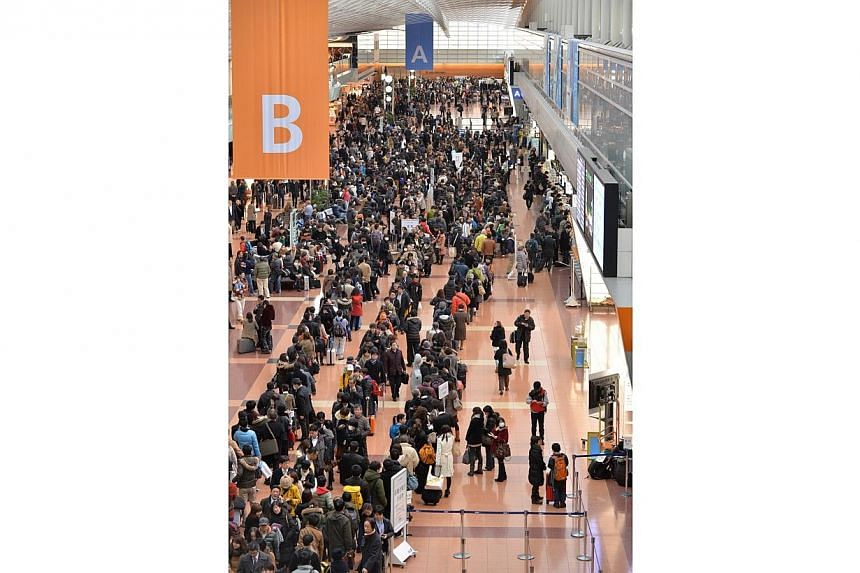 Passengers gather in front of a check-in counter at Tokyo's Haneda airport, on Feb 15, 2014. -- PHOTO: AFP