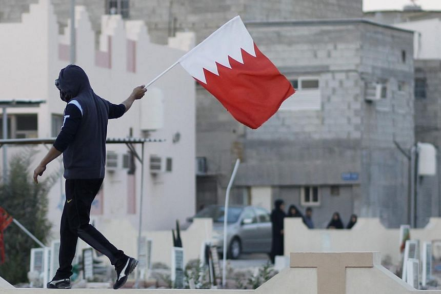 An anti-government protester waves a Bahraini flag in the village of Jidhafs, west of Manama, on Feb 14, 2014.A Bahraini policeman died of wounds sustained in a bomb blast during protests marking the anniversary of a crushed 2011 uprising as su