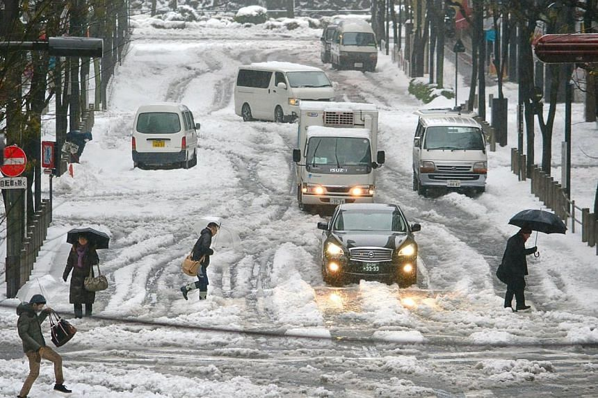 Pedestrians cross a street in the snow in Tokyo, on Saturday, Feb 15, 2014.Japan's road, rail and air travel services faced further disruptions on Saturday, reports and officials said, after a fresh snow storm killed three people and injured 85