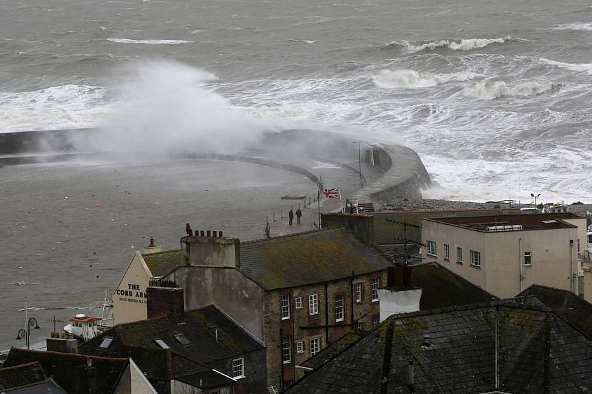 Waves crash over the Cobb harbour in Lyme Regis, southern England, on Feb 14, 2014.Transport networks suffered major disruption and more than 140,000 homes were without power across storm-battered Britain on Saturday, Feb 15, 2014 after the cou