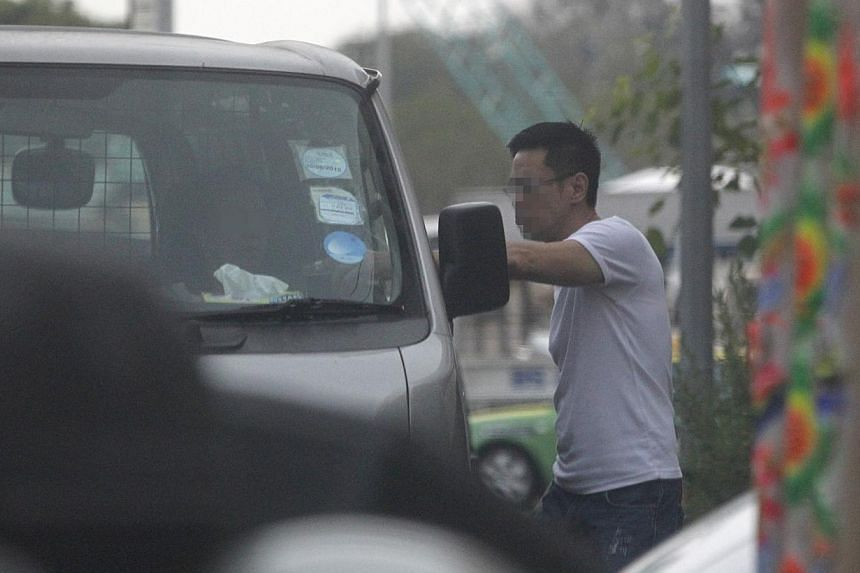 One of the three suspects arrested during Friday's raid waiting to board a police vehicle. A total of 2.9 million packets of contraband cigarettes were seized last year, almost double the 1.5 million packets confiscated in 2012.  One of the three sus
