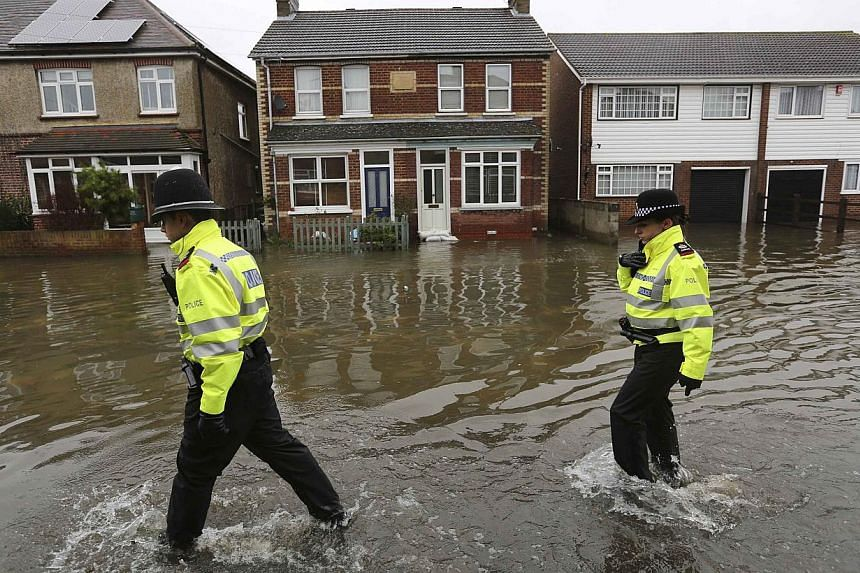 Police officers walk down a street in Egham after the River Thames burst its banks in south-east England on Feb 14, 2014. Sodden communities along the River Thames braced for more floods on as Britain counted the cost of a storm that claimed several