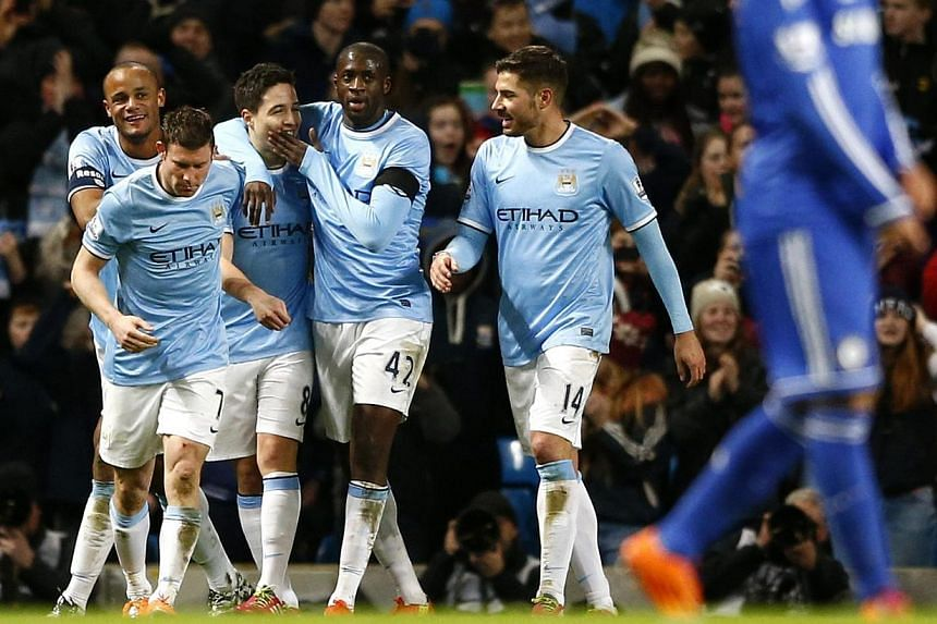 Manchester City's Samir Nasri (centre) celebrates with team mates after scoring a goal against Chelsea during their English FA Cup fifth round match at the Etihad Stadium in Manchester on Feb 15, 2014. City avenged their recent loss to Chelsea in the