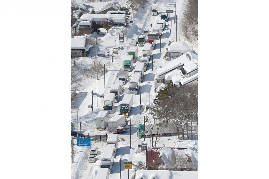 Trucks and cars are stranded by heavy snow on a national road in Karuizawa, on Sunday, February 16, 2014. Hundreds of cars are stuck on a hillside trunk road in Japan after it was hit by a snowstorm which is now heading north, officials said on
