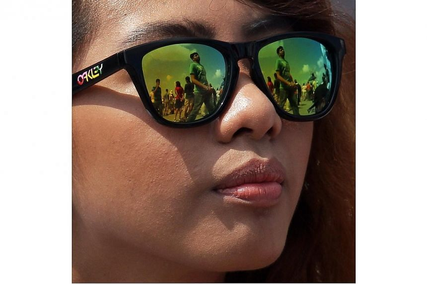 A member of the public watches the morning aerial display at the Singapore Airshow 2014 on Sunday, Feb 16, 2014. -- ST PHOTO: NEO XIAOBIN