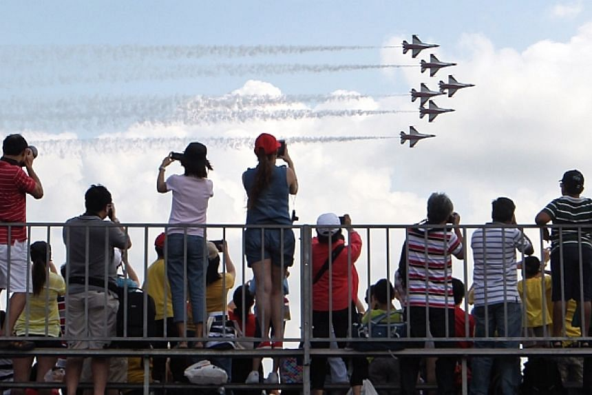 Members of the public watch the morning aerial display by the Air Force Black Knights, a six-ship formation display, at the Singapore Airshow 2014 on Sunday, Feb 16, 2014. -- ST PHOTO: NEO XIAOBIN
