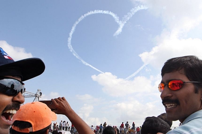 Mr Thangaraju Suresh (extreme left), 32, and Mr Selvam Sivaraman (extreme right), 30, react during the heart-shaped aerial display formation by the Air Force Black Knights at the Singapore Airshow 2014 on Sunday, Feb 16, 2014. They are part of a grou
