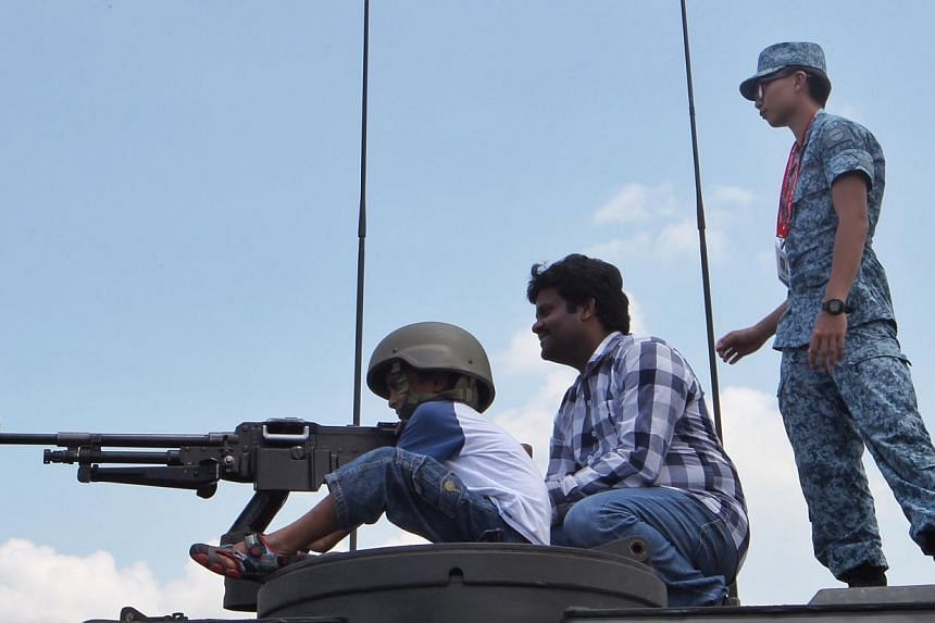 Seven-year-old Kushal Kota (left) tries out the machine gun on the V200A Armoured Fighting Vehicle together with his father Mr Subbarao Kota, 39, at the Singapore Airshow 2014 on Sunday, Feb 16, 2014. -- ST PHOTO: NEO XIAOBIN