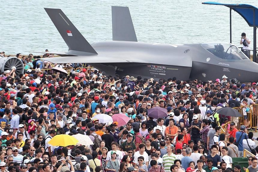 Members of the public surround the Lockheed Martin F-35 Lightning II stealth fighter plane on display at the Singapore Airshow 2014 on Sunday, Feb 16, 2014. -- ST PHOTO: NEO XIAOBIN