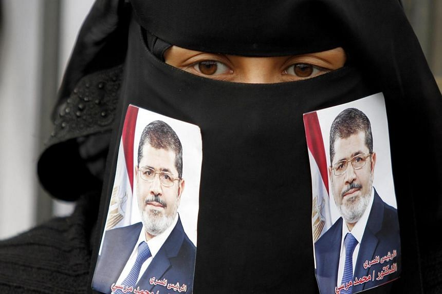 A pro-democracy demonstrator is seen with pictures of Egypt's ousted president Mohamed Mursi on her face veil during celebrations to mark the anniversary of an uprising against the regime of former president Ali Abdullah Saleh in Sanaa, Feb 11, 2014.