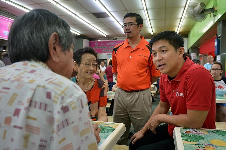 Acting Manpower Minister Tan Chuan-Jin (right) speaking with Mr Lim Poh Kwee, 80 (left) and his wife Madam Ang Soh Hiok, 74 (2nd from left) at a coffeshop during his walkabout at Pasir Ris East. Mr Tan sought to explain the tension between keeping Si