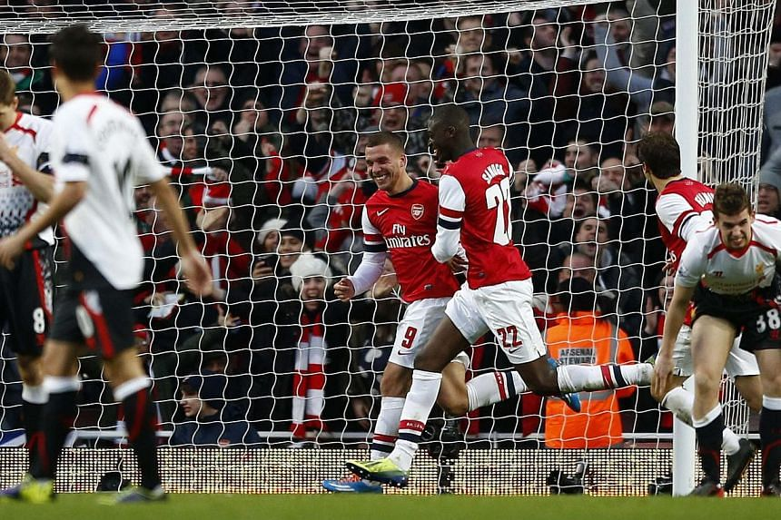 Arsenal's Lukas Podolski (third from left) celebrating his goal against Liverpool with team mate Yaya Sanogo during their FA Cup fifth round match at the Emirates Stadium in London on Feb 16, 2014. Arsenal knocked Liverpool out of the FA Cup with a 2