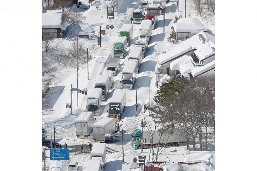 Trucks and cars are stranded by heavy snow on a national road in Karuizawa on Feb 16, 2014. -- PHOTO: REUTERS