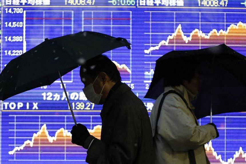 Pedestrians holding umbrellas walk past an electronic board outside a brokerage in Tokyo on Feb 4, 2014. -- FILE PHOTO: REUTERS